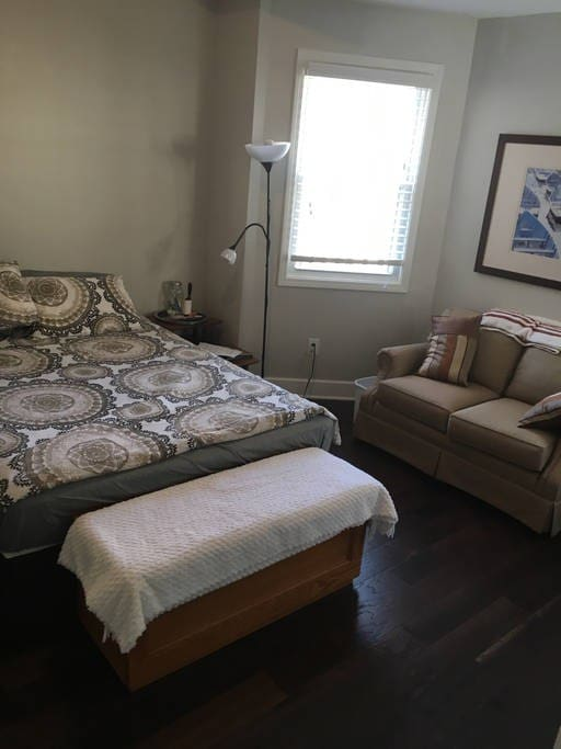 Your bedroom features a comfortable queen bed, love seat, iron/ironing board, house manual, water, snacks, toiletries, and brochures about our favorite Indy attractions.