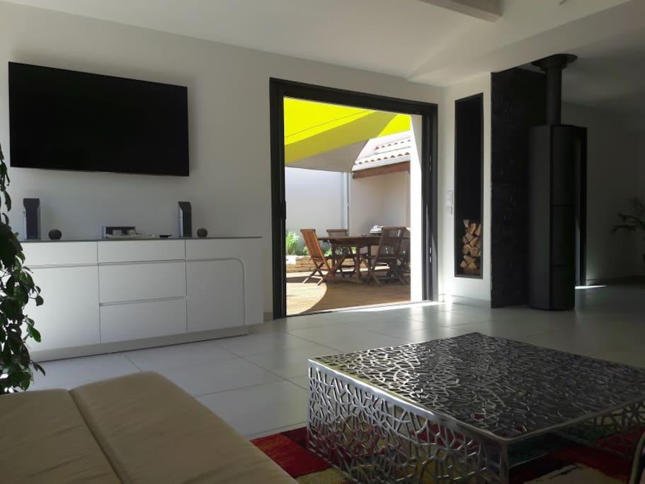salon avec écran plat de  140cm , Baies à galandages pour ouverture sur l'extérieur