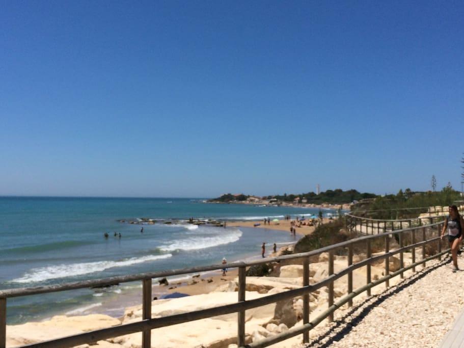 Spiaggia di Caucana in prossimità degli scavi archeologici. Sullo sfondo il faro di Punta Secca.