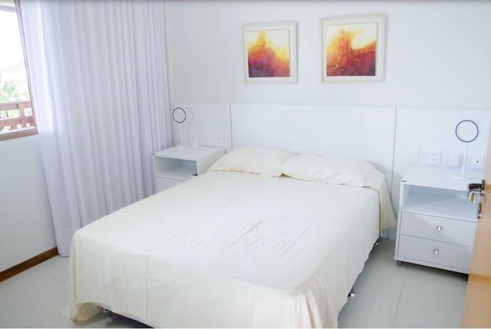 Quarto de casal com ar condicionado split, TV, guarda roupa e cabides, roupa de cama e banho disponíveis.