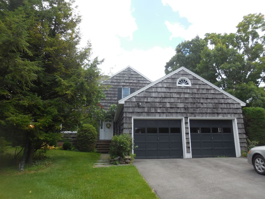 House has wooden deck, attached 2 car garage, on about acre of flat land
