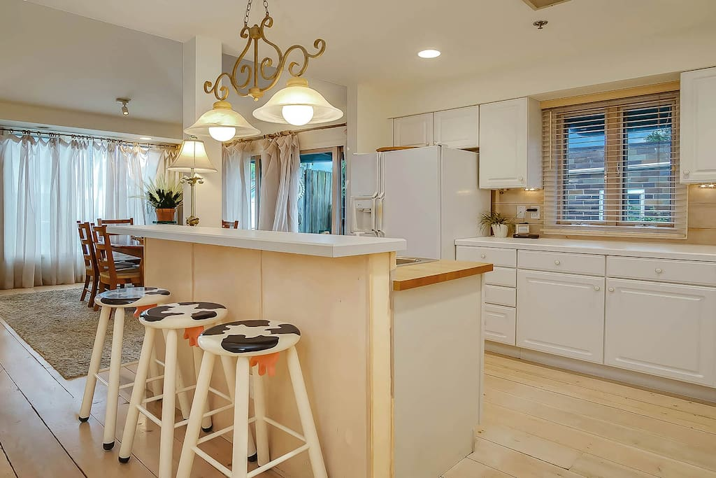 The open kitchen has a breakfast bar with three stools.