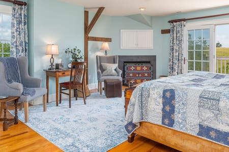 Gas fireplace, flat screen tv, private bathroom with jacuzzi tub and walk-in shower, kitchenette, premium mattress, pillows, and linens, french doors open out to private porch with views of rolling hillsides.