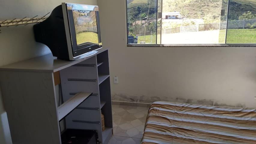 Quarto 1 com cama de casal, estante e tv.