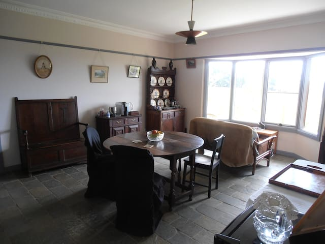 The Guest breakfast room and lounge has lovely views across the paddocks and mountains and is furnished with antiques