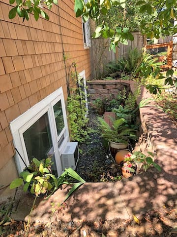 A large garden well gives you a plant filled view from the living room and kitchen sink areas.   A sturdy wooden bench is in the middle for facilitating egress.  A quiet A/C unit is in the small window during the hottest summer months.