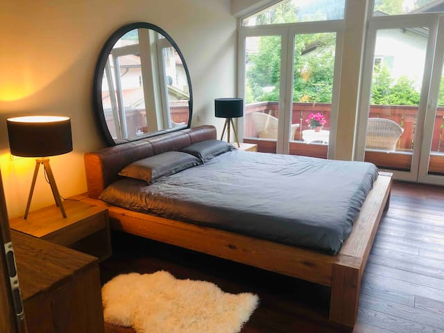 Master bedroom with a balcony and a gorgeous view of Alpspitze,  Zugspitze and Hausberg mountains