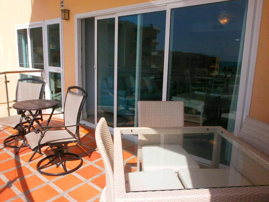 Outdoor furniture on the balcony, including 2 swivel chairs with table and 4-seat dinning table.