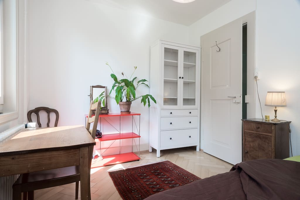 Guest room furnished with double bed, nightstand, closet, shelf, desk and clothes rack.