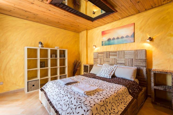Master bedroom with double bed and walk-in wardrobe, with entrance door and door to balcony. / Dormitorio principal con cama de matrimonio y armario vestidor, puerta al balcón.