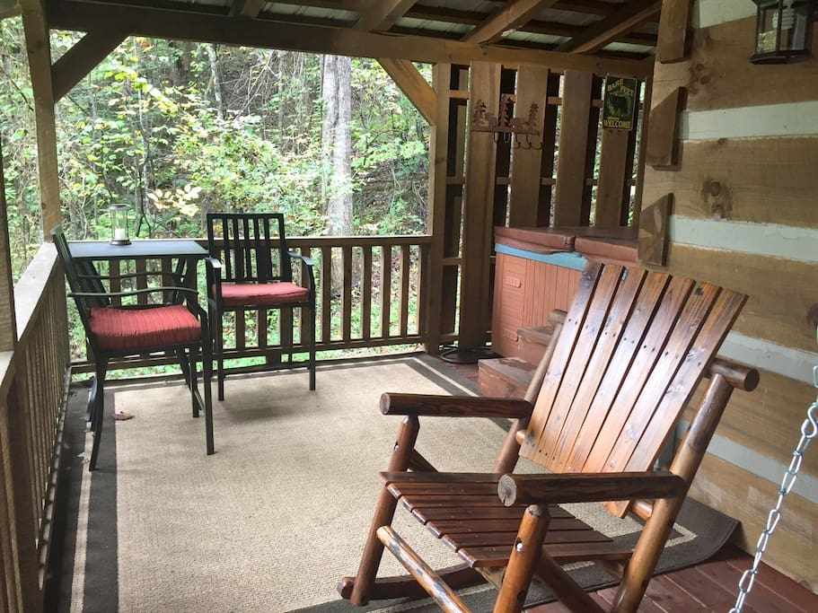 Large covered deck with swing, rocker, seating area and hot tub.
