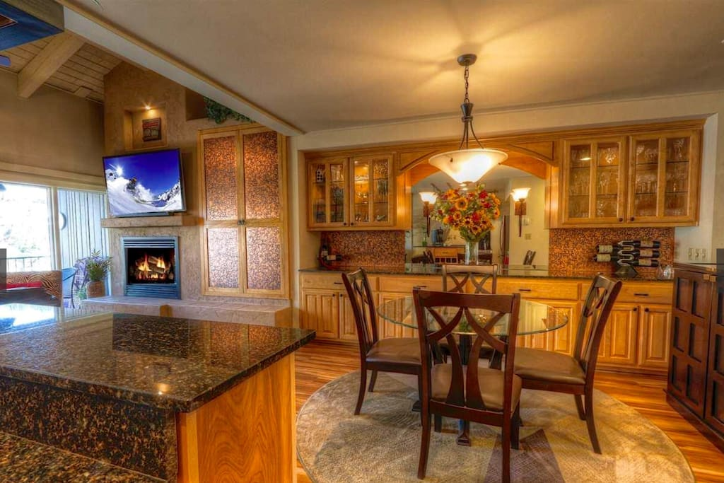 The dining area and edge of kitchen showing beautiful cabinetry and granite countertops.