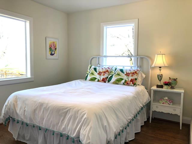Front bedroom has queen-sized bed and pretty antique furnishings and original art.  Bright and airy with room darkening shades. The bed has a Layla memory foam mattress, a feather duvet, feather pillows and all bedding is 100% cotton.