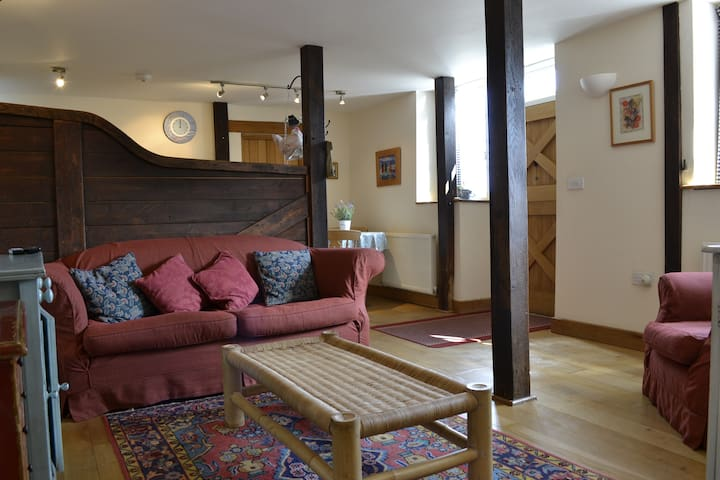 The open plan sitting room/kitchen diner, featuring original stables partitions.