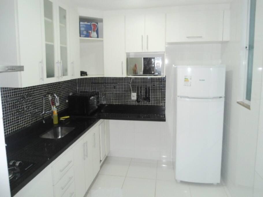Cozinha bem ampla com geladeira, forno, microondas e liquidificador.
