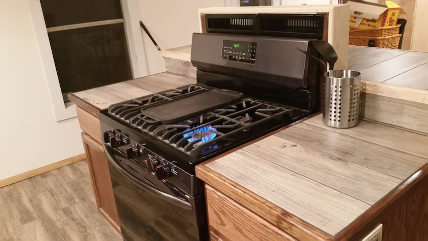 5 burner gas range that is island set against the bar and in front of the sink