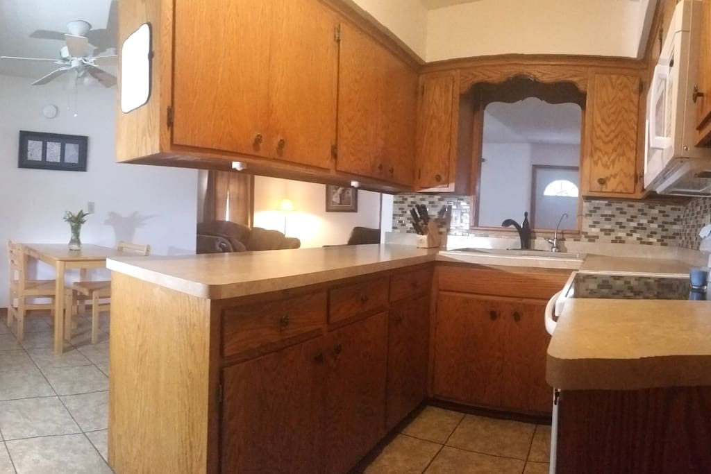 Fully stocked kitchen with stove and microwave.