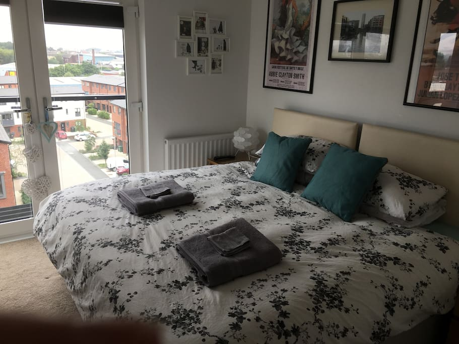 Super king bed for couples. Can be setup as two singles for friends (zip bed) and ensuite with shower over bath, sink, and toilet. Juliet balcony overlooking city skyline. Lovely views especially at night. West facing for fantastic sun set views.