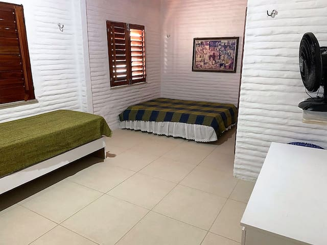 Ampla suite com cama de casal e solteiro e espaço para redes