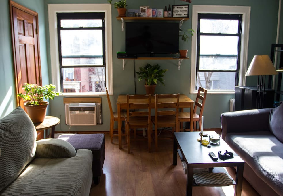 The living room is quite massive, and comes fully furnished with two couches, coffee table, ottoman, end shelves, and an elegant pine dining table with four chairs.