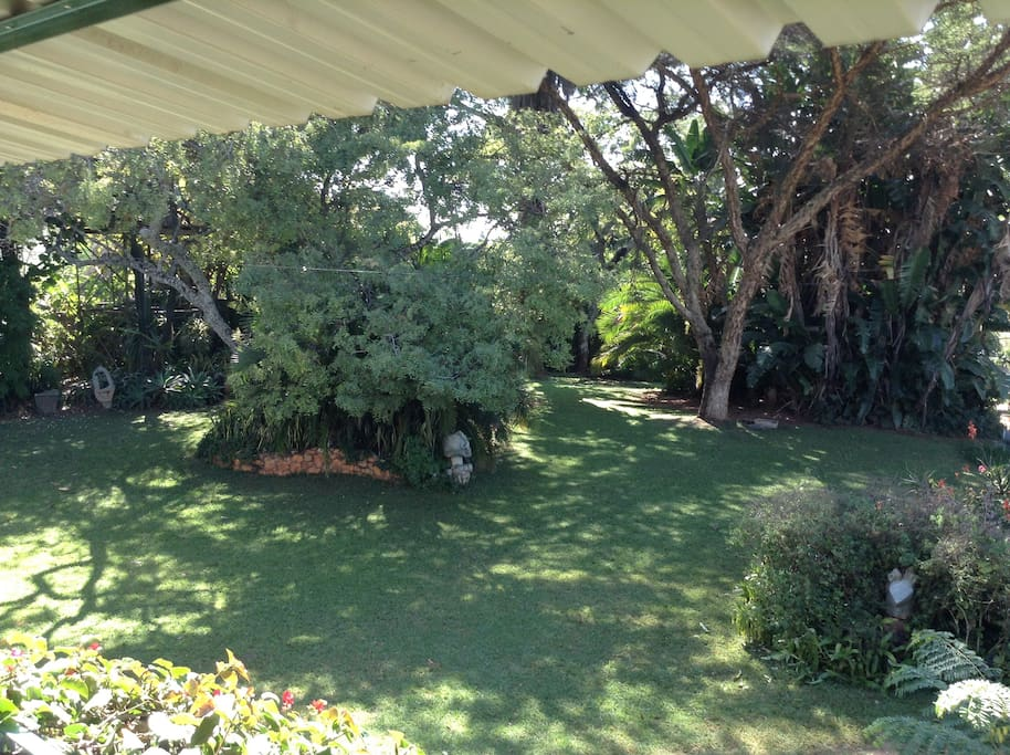 Camping area under large trees by the main house .