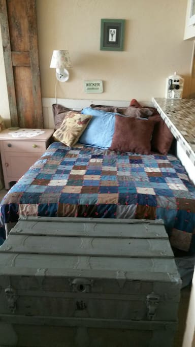 Luxurious double bed for extra guests next to couch in living room,