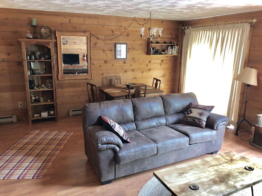 Living room, dining room, sliding glass door to deck, shelf with handmade pottery.