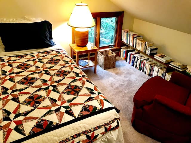 Loft bedroom with comfortable chair, books, closet, and a nice view of the woods. Queen-size bed on main level.