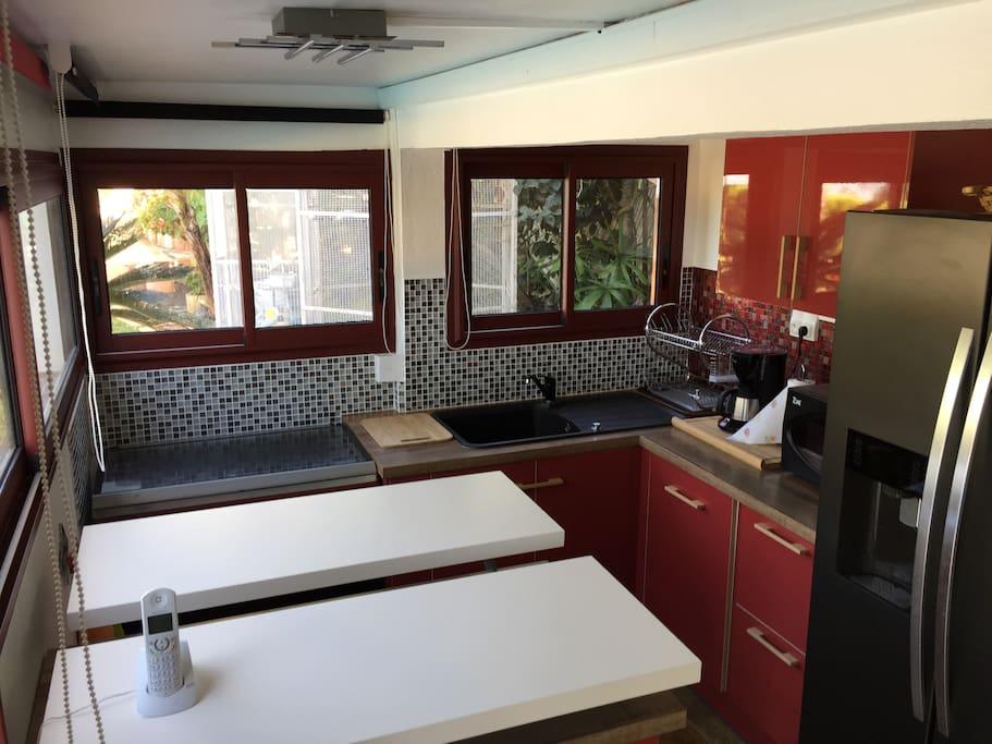 Cuisine ouverte sur salon toute équipée, 4 feux, micro-ondes, réfrigérateur américain, cafetière, ...