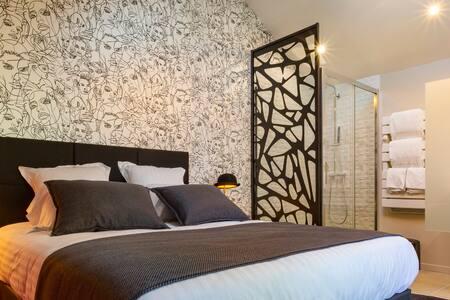 This cosy first-floor bedroom with a high ceiling is full of light and features bold colours and an ultra-modern designer style. Nichée à l'étage de la maison, cette chambre lumineuse aux couleurs vives, à la décoration design et contemporaine.