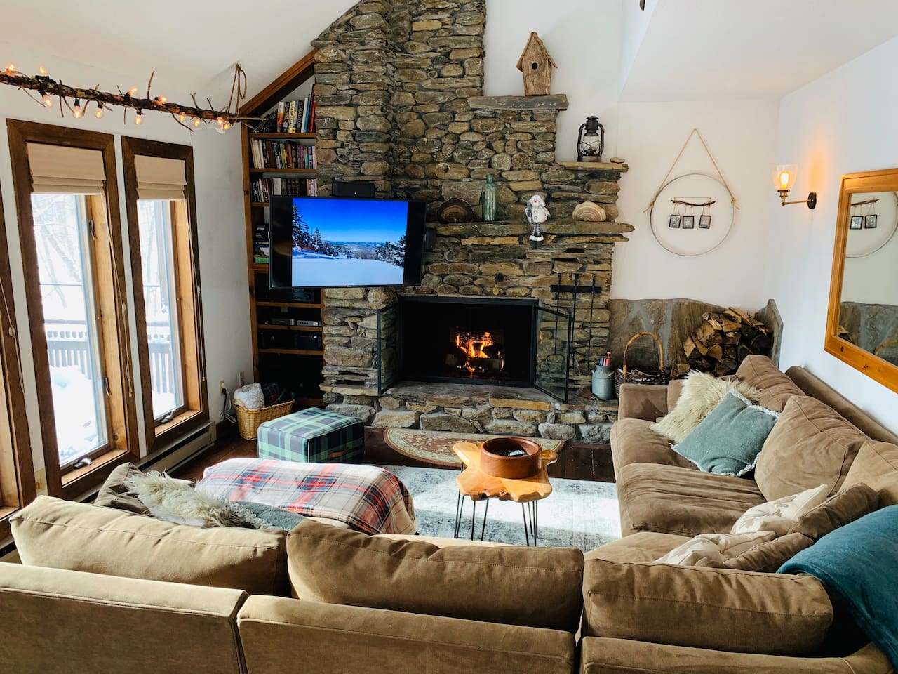 """Our main living room with cozy seating and fieldstone fireplace with views. Guests say: """"As soon as you walk in you feel comfortable. The decor adds a cozy feeling and the little touches just brought it up a notch."""""""