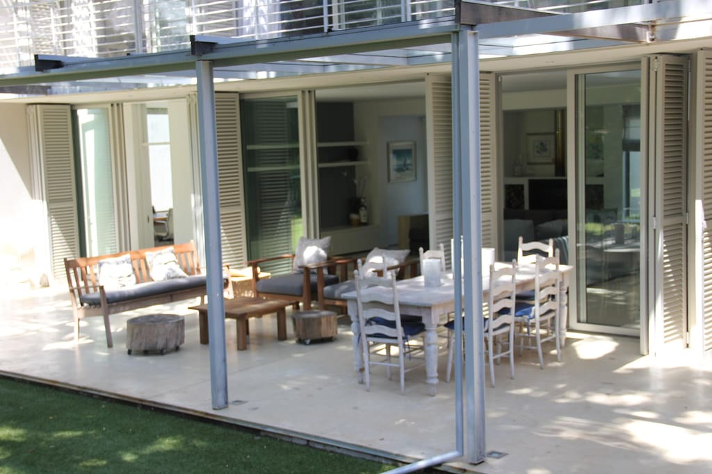 Glass covered verandah with outside seating and dining, looking on to Table Mountain.