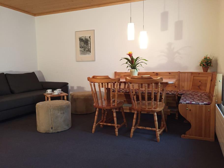 Wohnzimmer mit Bett-Sofa und Tisch