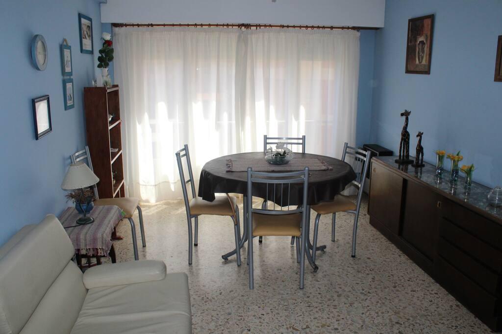 Living con balcom francés, mesa redonda con 4 sillas, velador y un sofá cama de una plaza