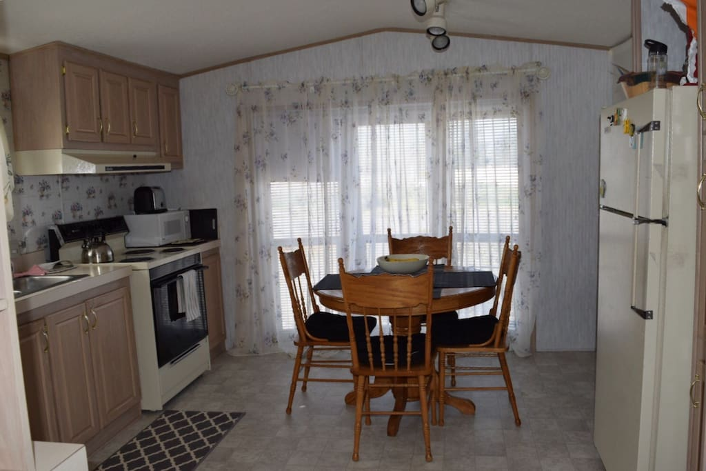 Sunny kitchen has all appliances, dishwasher, microwave, coffee maker, some snacks and drinks.