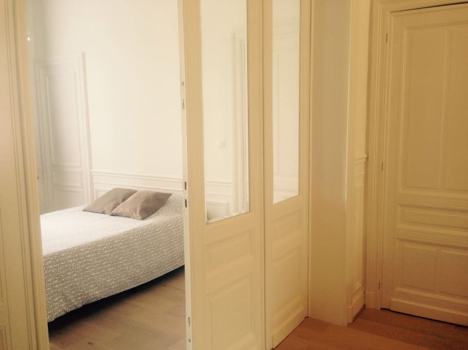 The large and bright bedroom with a double bed, antique mirror, tv,...