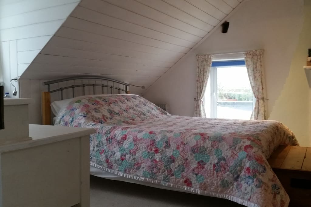 King size double bed with glimpse of the sea