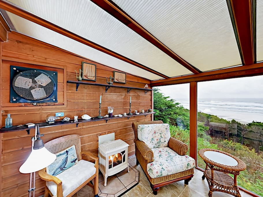 The sunroom off of the master suite features seating, a fireplace, and stunning ocean views through floor- to-ceiling windows.