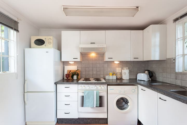 Full kitchen with microwave, fridge/freezer, oven with four plate stove top and washing machine.
