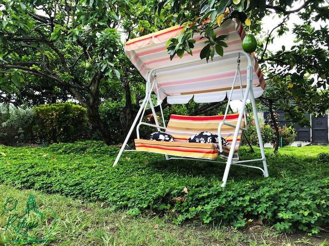 Silla mecedora para parejas bajo los árboles frutales de la villa