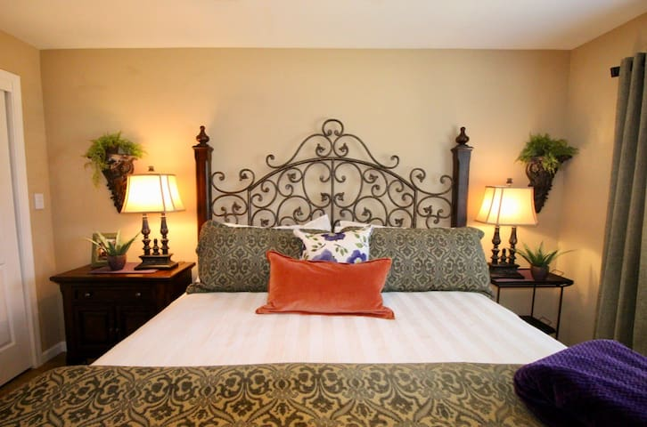 Guest Bedroom #1 with Iron and wood bed, luxury bedding, night tables, lamps and clock radio with charging station for your phone and more.