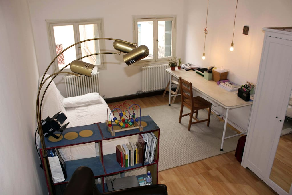 Zona giorno con scrivania e divano letto per due persone.