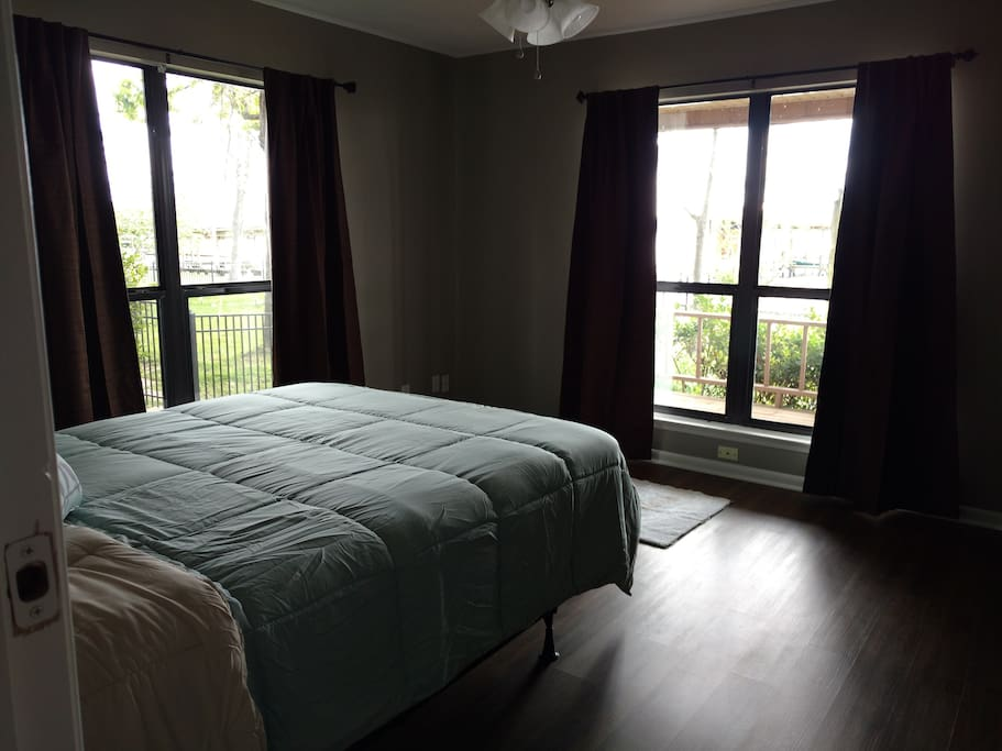 Another view of 1st downstairs bedroom with lake view and ceiling fan.