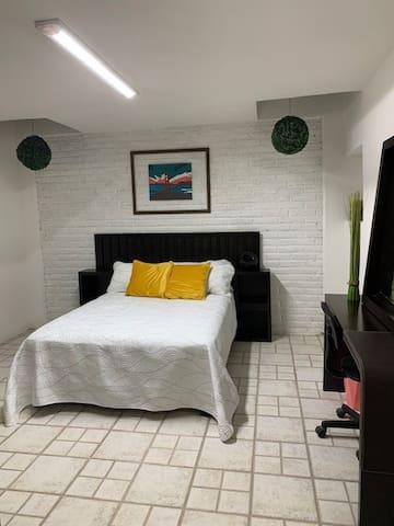 habitación con cama matrimonial y espacio de trabajo