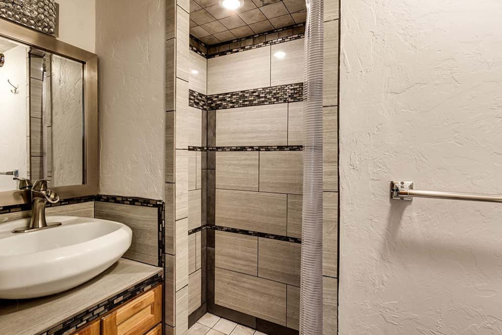 Fancy new double shower and cute vanity.  Steve admits he spent too much time on the glitzy  tile design. The lights are automatic and inviting,  The farm faucet on the sink could spray you if your in a bad mood.  Has happened...