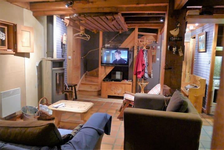 Le coin télévision , le poële à bois en pierre oellaire , l'escalier d'accès à la chambre . A partir de novembre 2019 , ce coin sera équipé de trois fauteuils Stressless en cuir .