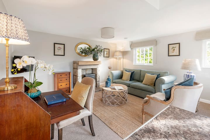 Airy and  comfy sitting room.  Three seater sofa, electric wood burner.  A very tranquil setting where you can see the local birds on the feeders just outside the cottage.  A lovely view over the valley  and over the Manor garden (sorry no access)