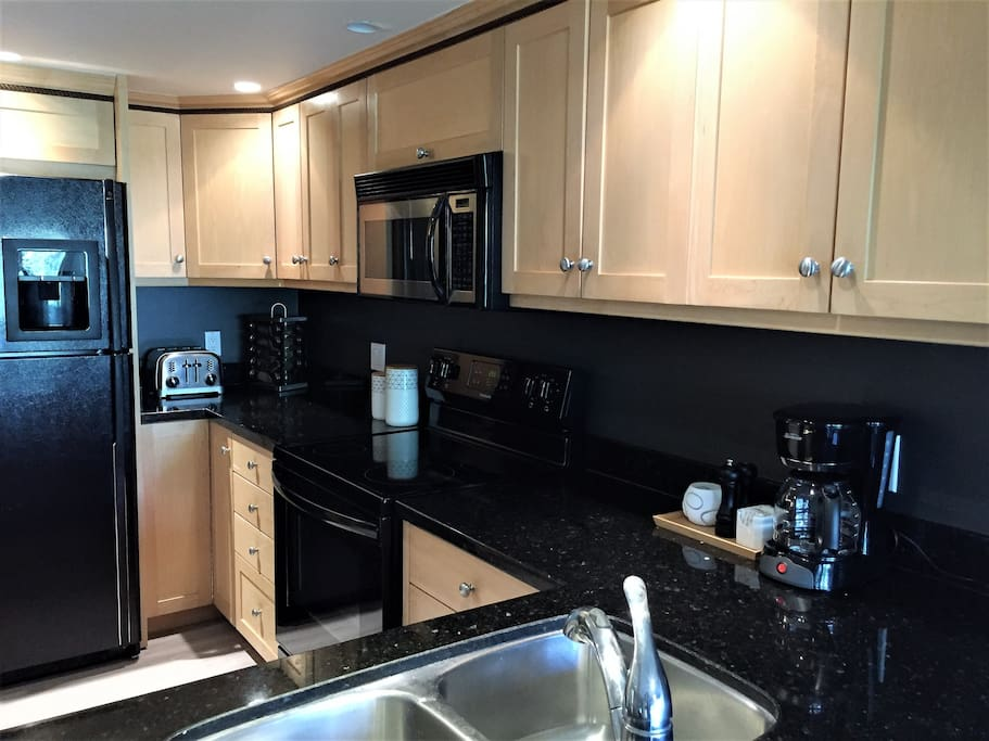 Kitchen with brand new convection range, granite counter tops, and automatic ice & water dispenser.