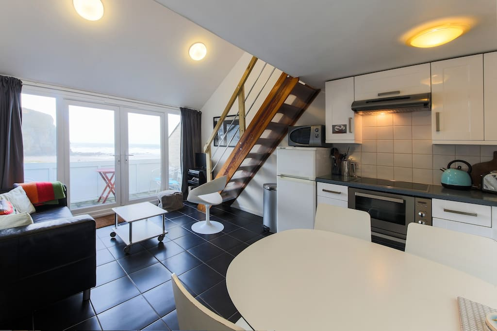 Open plan living/dining/kitchen area, leading to the balcony, overlooking the beach and sea.