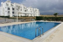 Just in front of your balcony - pool and sunbeds